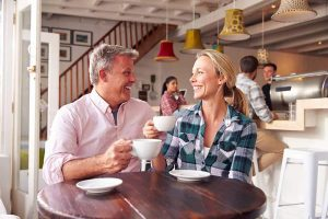 A man and a woman are on a coffee date, happy and healthy because of oral cancer screening.